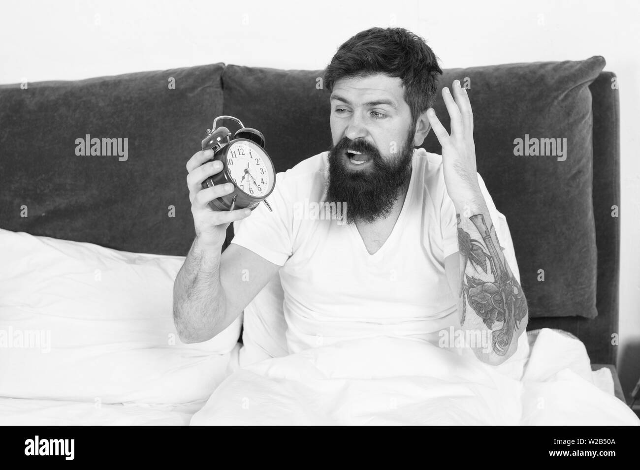 Get up with alarm clock. Overslept again. Tips for waking up early. Tips for becoming an early riser. Man bearded hipster sleepy face in bed with alarm clock. Problem with early morning awakening. - Stock Image