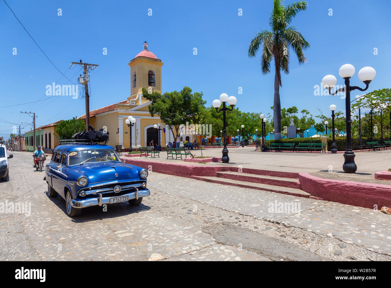 Trinidad, Cuba - June 6, 2019: View of an Old Classic American Car in the streets of a small Cuban Town during a vibrant sunny day. Stock Photo