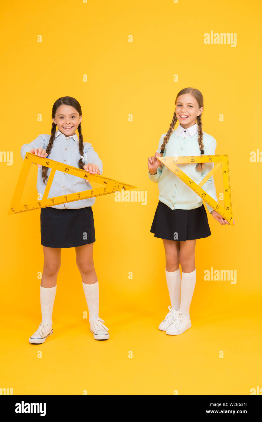 Kids cute students study math. Knowledge day. Move from theory to practice. Excellent pupils. Secondary school. Schoolgirls tidy appearance school uniform hold big rulers for geometry school lesson. - Stock Image