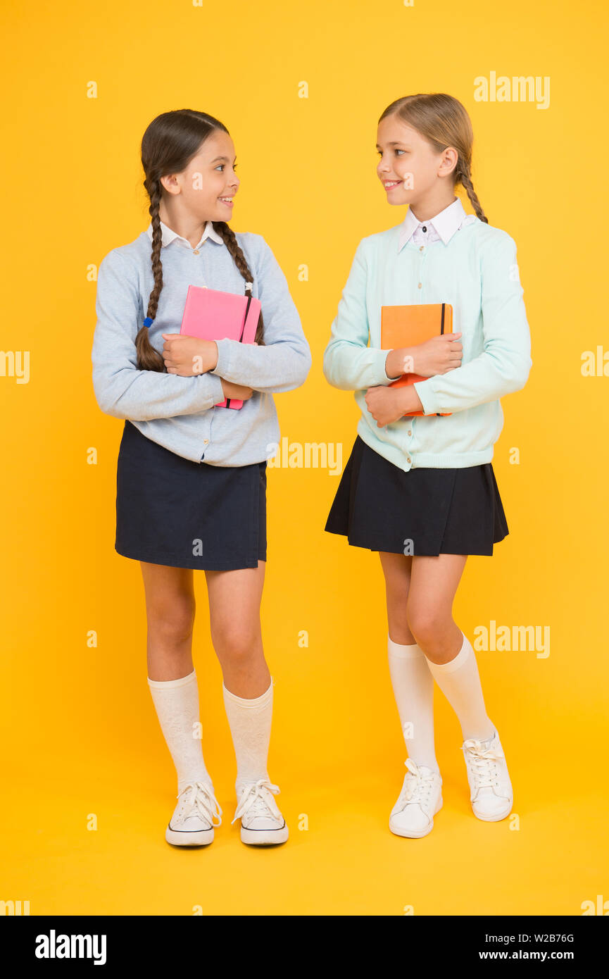 Knowledge day. Schoolgirls best friends excellent pupils. Secondary school. Schoolgirls tidy appearance school uniform. School friendship. School day fun cheerful moments. Kids cute students. - Stock Image
