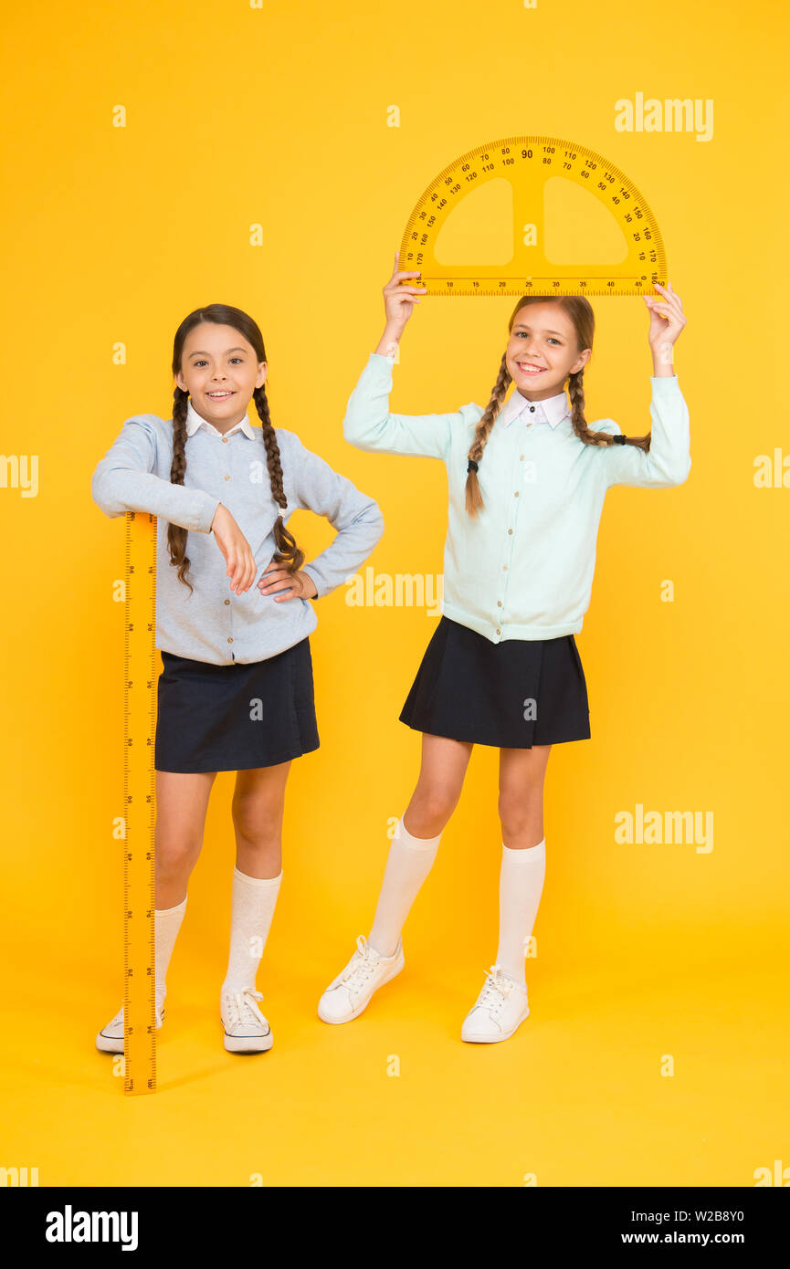 Move from theory to practice. Kids cute students study math. Knowledge day. Excellent pupils. Secondary school. Schoolgirls tidy appearance school uniform hold big rulers for geometry school lesson. - Stock Image