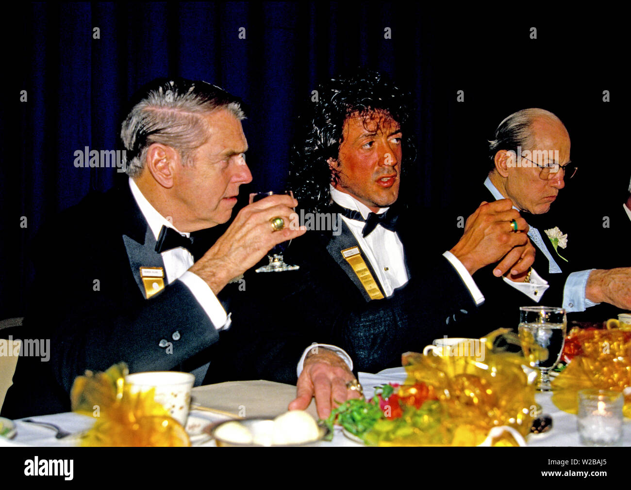 American actor, director, screenwriter, and producer Sylvester Stallone center, attends a dinner as he accepts the President's Council on Physical Fitness award at the Washington, DC Touchdown Club dinner in Washington, DC on January 23, 1988. At left is former Washington Redskins head coach George Allen and at right is Associate Justice of the United States Supreme Court Byron R. 'Whizzer' White.Credit: Arnie Sachs/CNP | usage worldwide - Stock Image