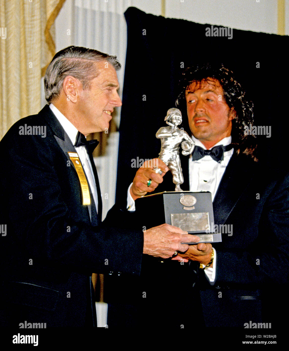 American actor, director, screenwriter, and producer Sylvester Stallone, right, accepts the President's Council on Physical Fitness award from former Washington Redskins head coach George Allen, left, at the Washington, DC Touchdown Club dinner in Washington, DC on January 23, 1988. Credit: Arnie Sachs/CNP | usage worldwide - Stock Image