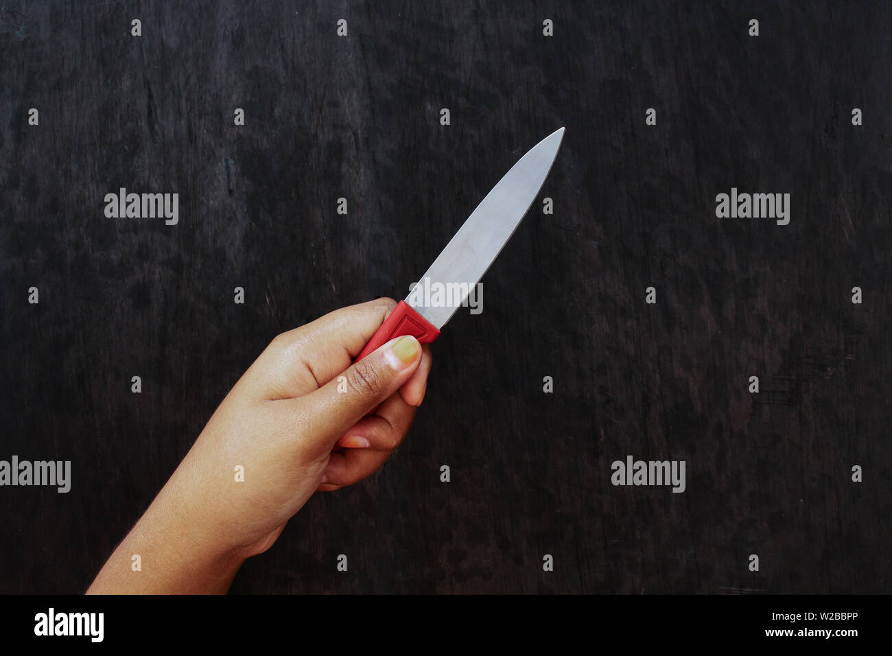 Brown Skin Girl Holding Knife on Black Wood Board Background Stock Photo