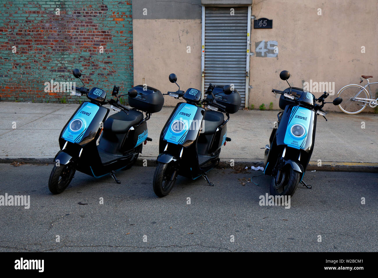 Revel dockless rental electric mopeds parked on a street