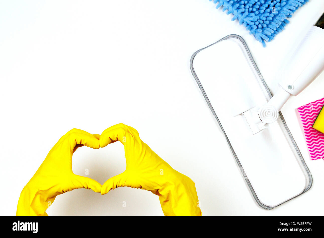 Housework, housekeeping, household, cleaning service concept. Cleaning spray mop, rags, sponges and woman hand with rubber gloves in the form of heart - Stock Image