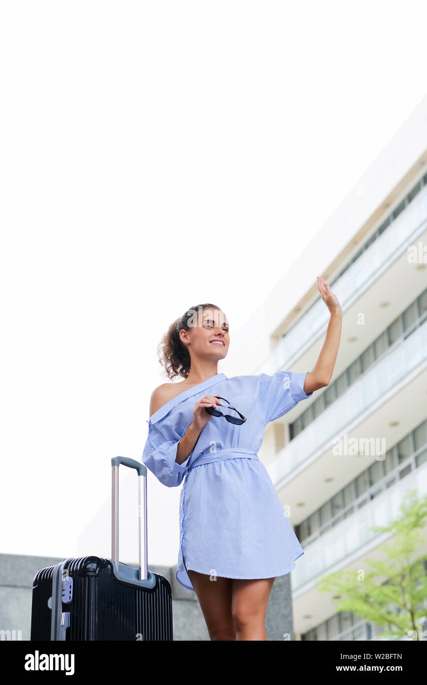 Attractive smiling young woman standing at her luggage and waving with hand to brig attention of taxidriver - Stock Image