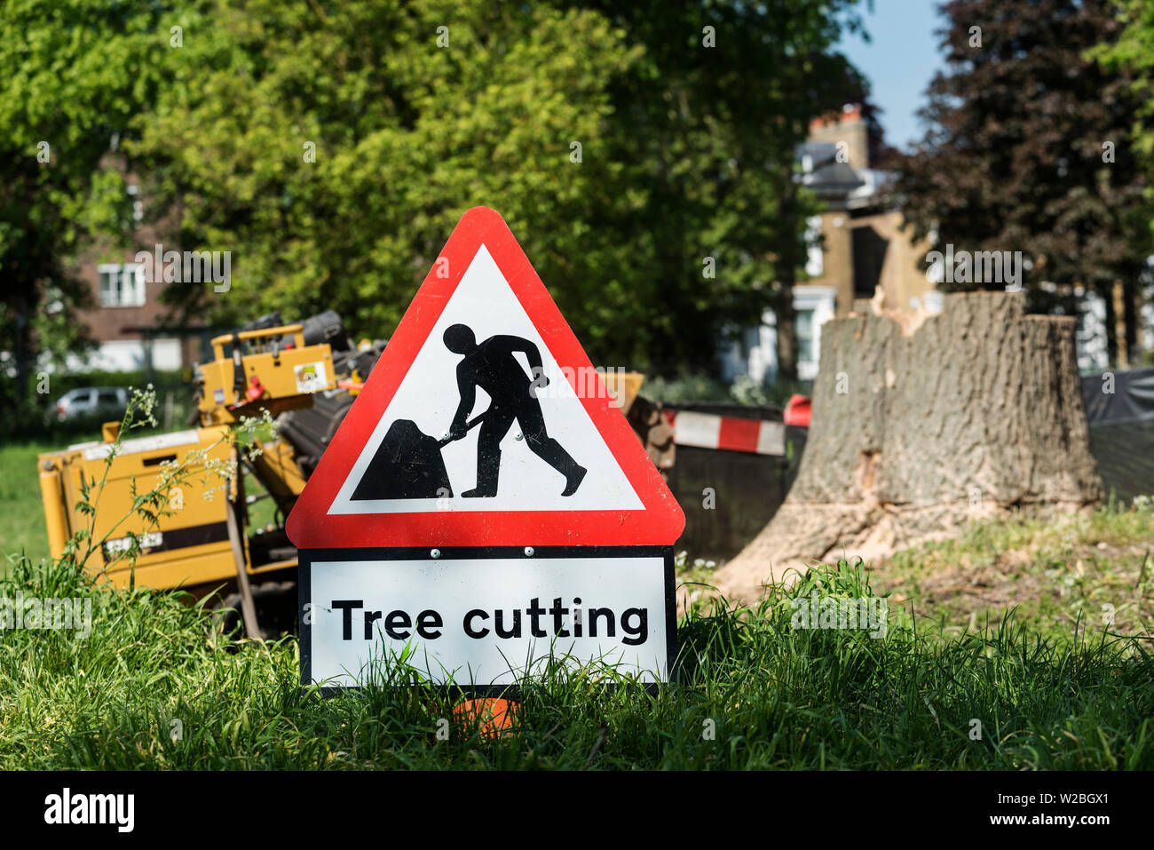 A sign warns of the hazardous area around tree cutting and a stump grinder. - Stock Image