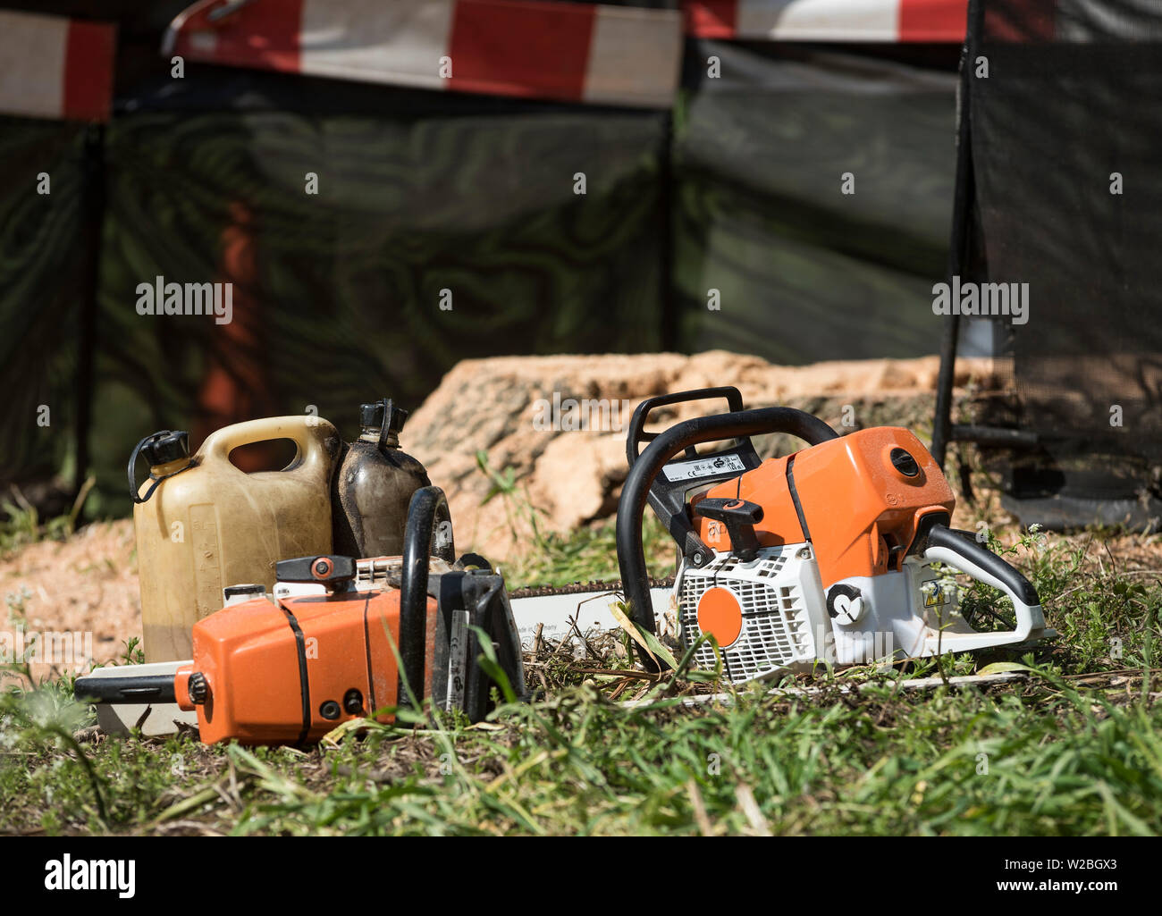 Two chainsaws sat in the grass about to be refueled. - Stock Image