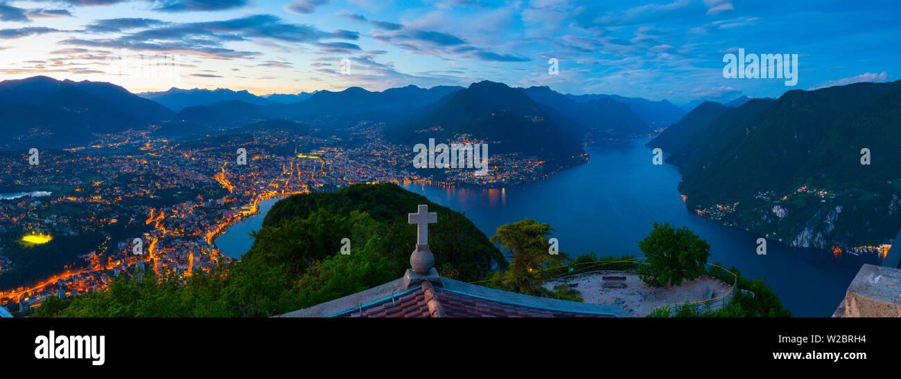 Elevated view over Lugano from Monte San Salvatore illuminated at Dusk, Lake Lugano, Ticino, Switzerland Stock Photo