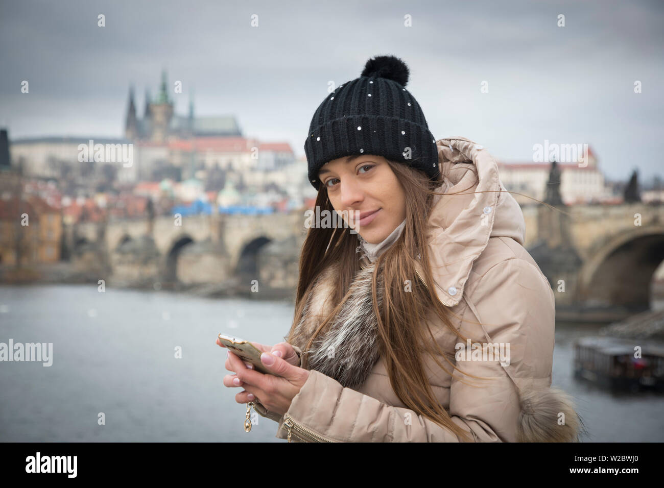 Young woman with smart phone by the Vltava river, Prague, Czech Republic (MR) - Stock Image