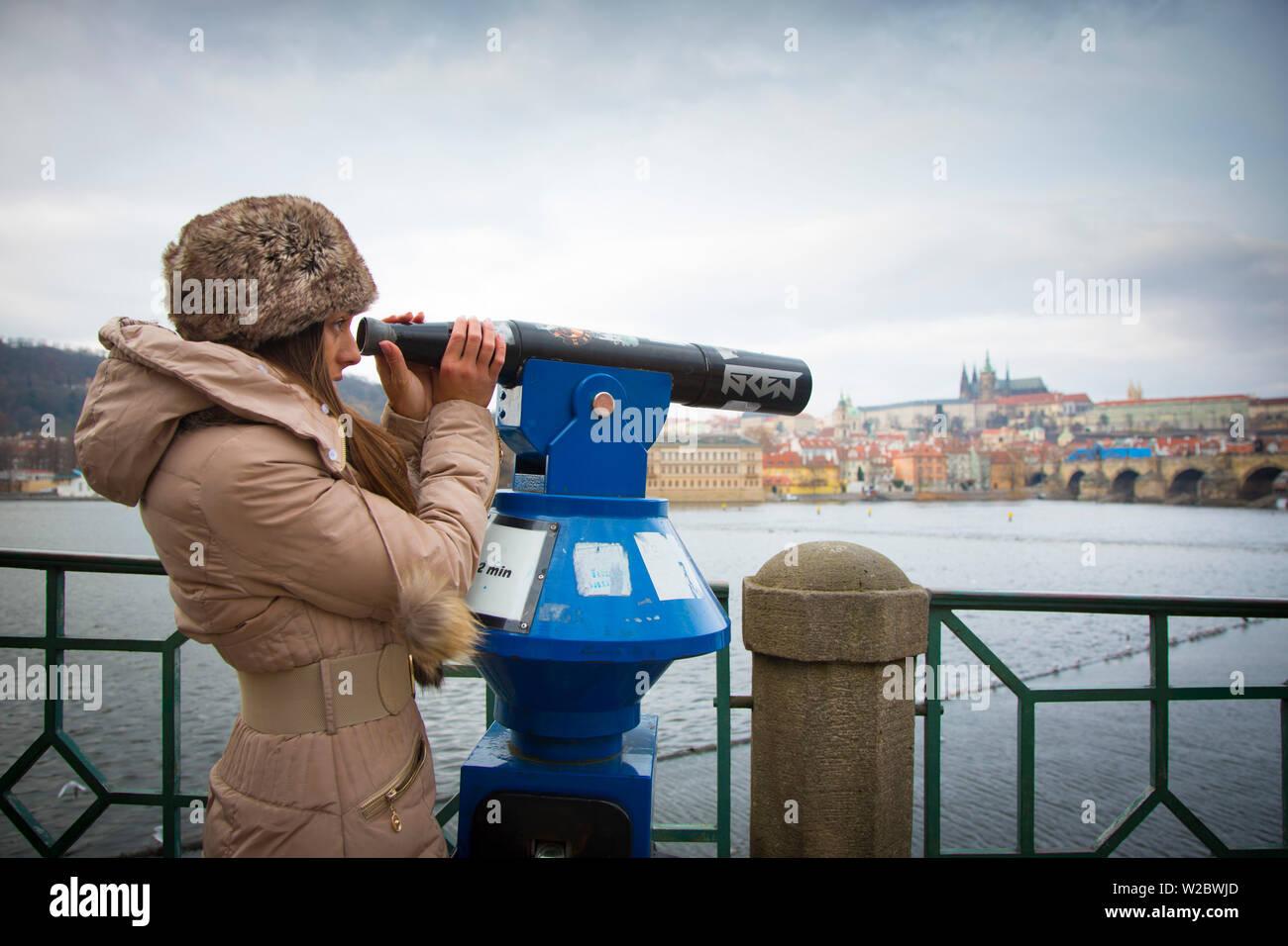 Young woman looking through telescope, Prague, Czech Republic (MR) - Stock Image