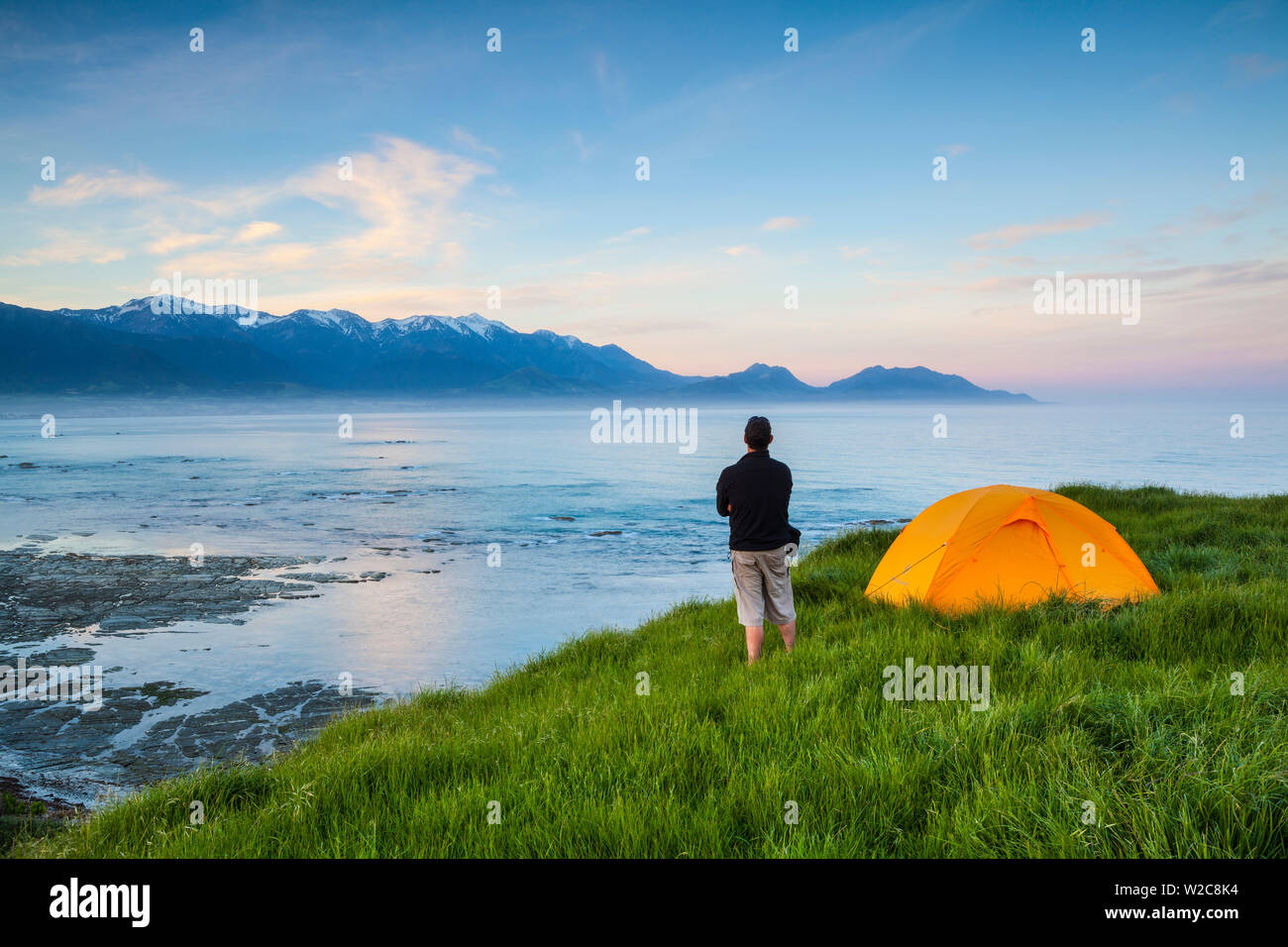Elevated view over Kaikoura illuminated at sunset, Kaikoura, South Island, New Zealand - Stock Image