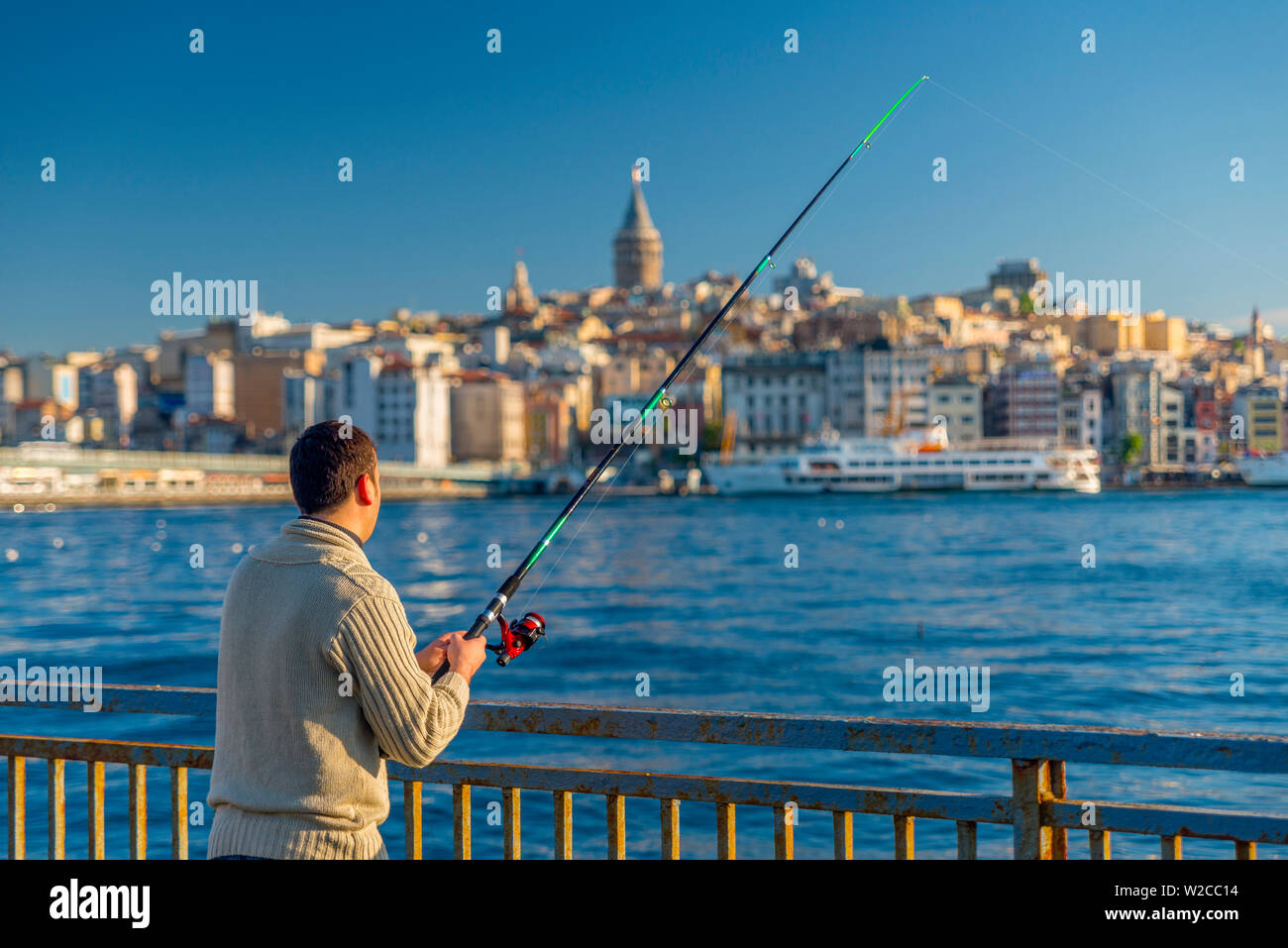 Turkey, Istanbul, Beyoglu, Golden Horn, Galata Tower in background, Man Fishing - Stock Image