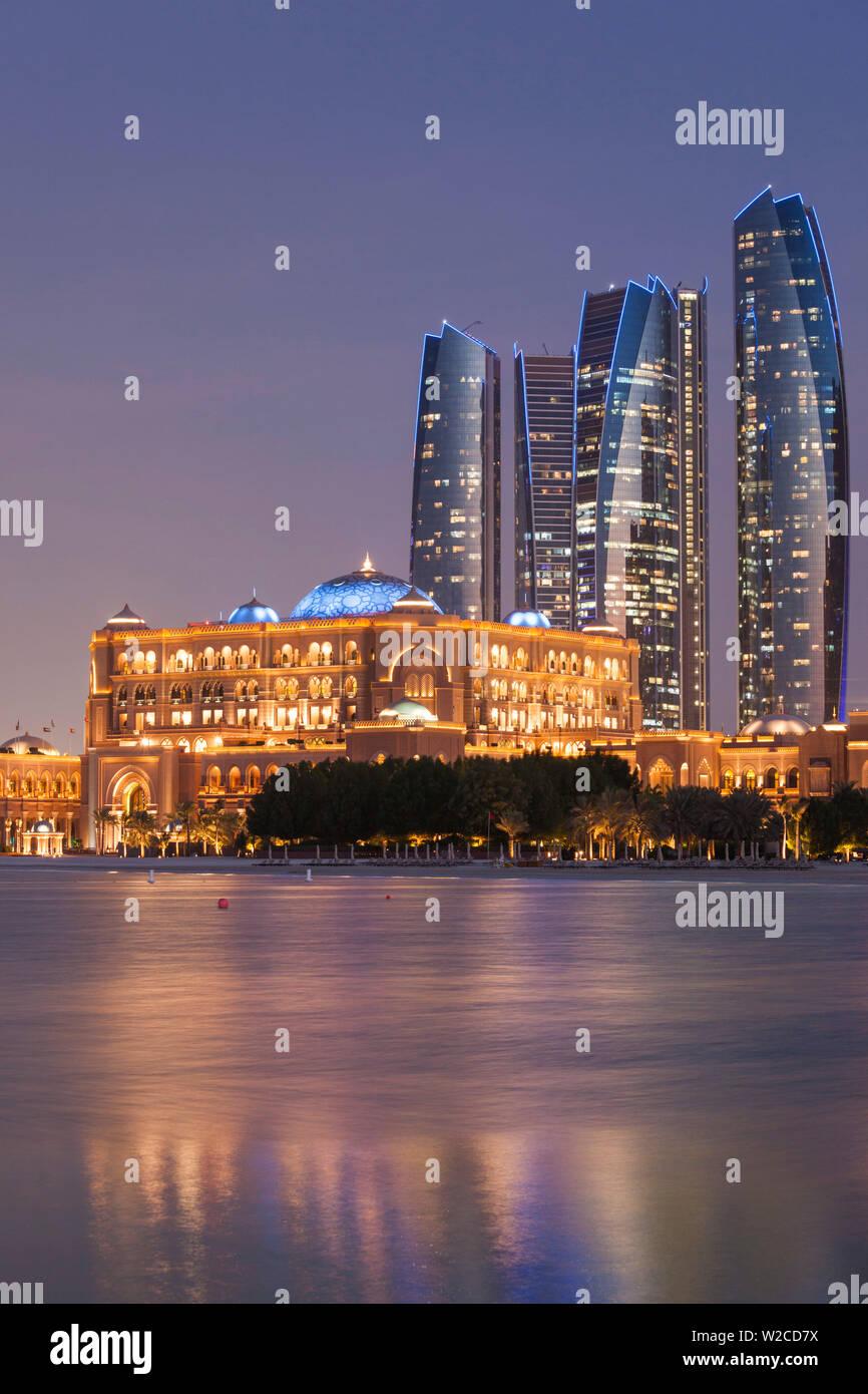 UAE, Abu Dhabi, Etihad Towers and Emirates Palace Hotel, dusk - Stock Image