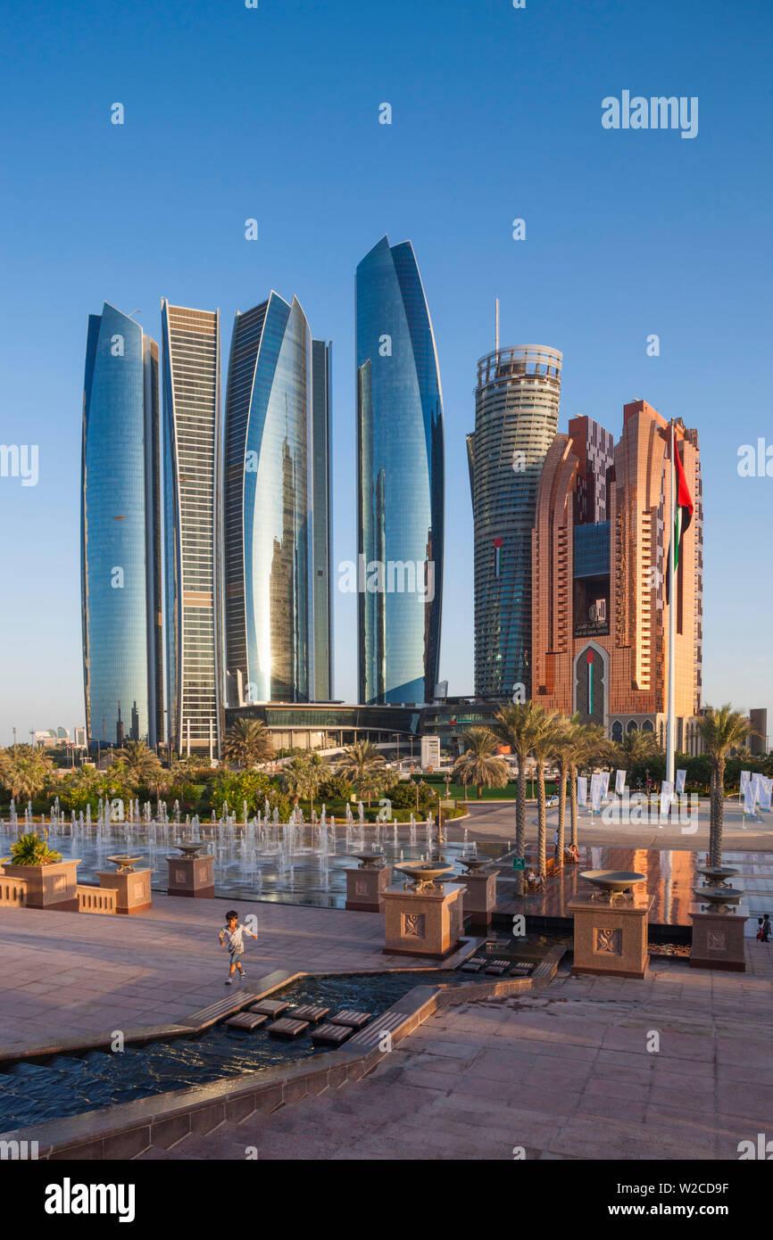 UAE, Abu Dhabi, Etihad Towers and Emirates Palace Hotel fountains, dusk - Stock Image