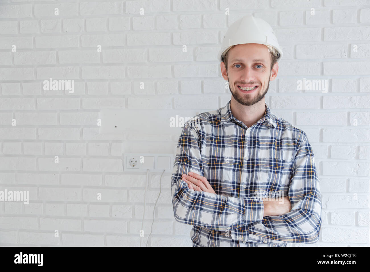 Portrait of happy young foreman with hard hat - Stock Image