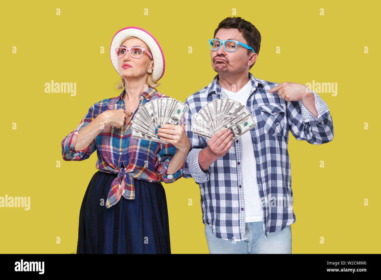 Couple of confident friends, adult man and woman in casual checkered shirt standing together holding fan of dollars and pointing fingers to themself w - Stock Image