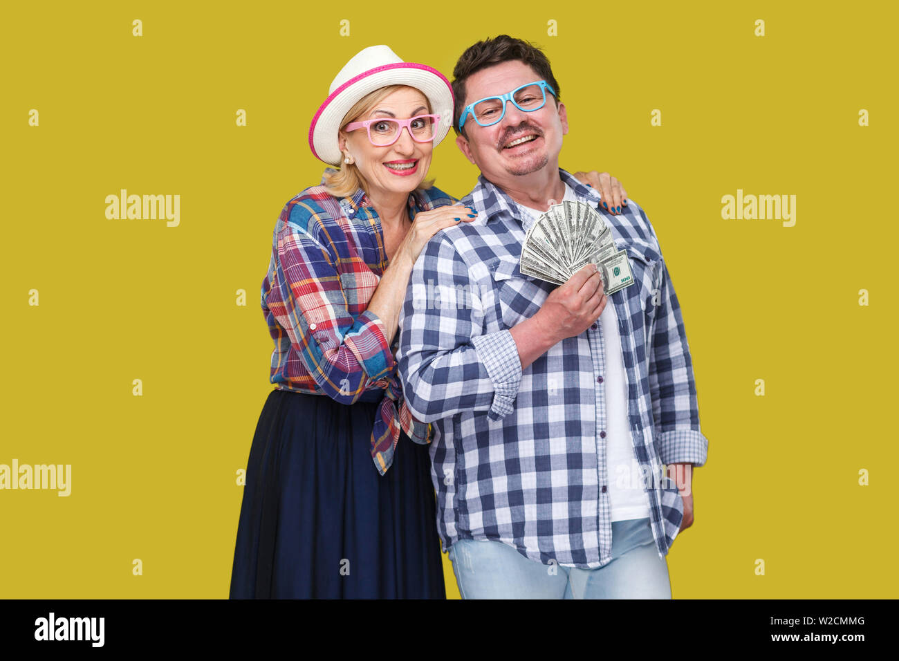Happy wealthy family, adult man and woman in casual checkered shirt standing pickaback together, holding fan of dollar, toothy smile, looking at camer Stock Photo