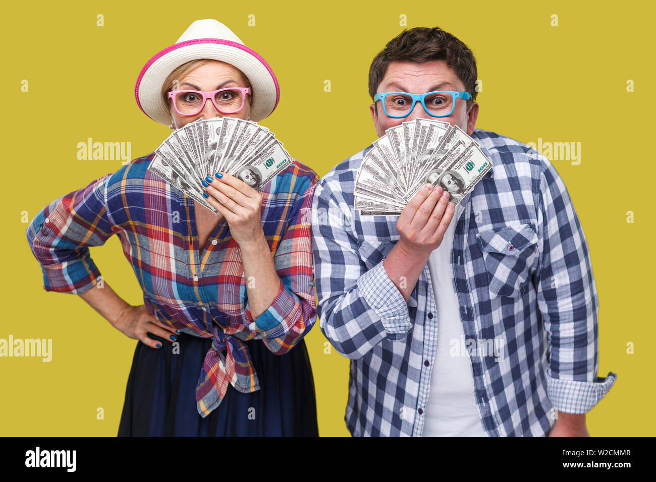 Couple of funny friends, adult man and woman in casual checkered shirt standing together holding, covering mouth with fan of dollars, looking at camer - Stock Image