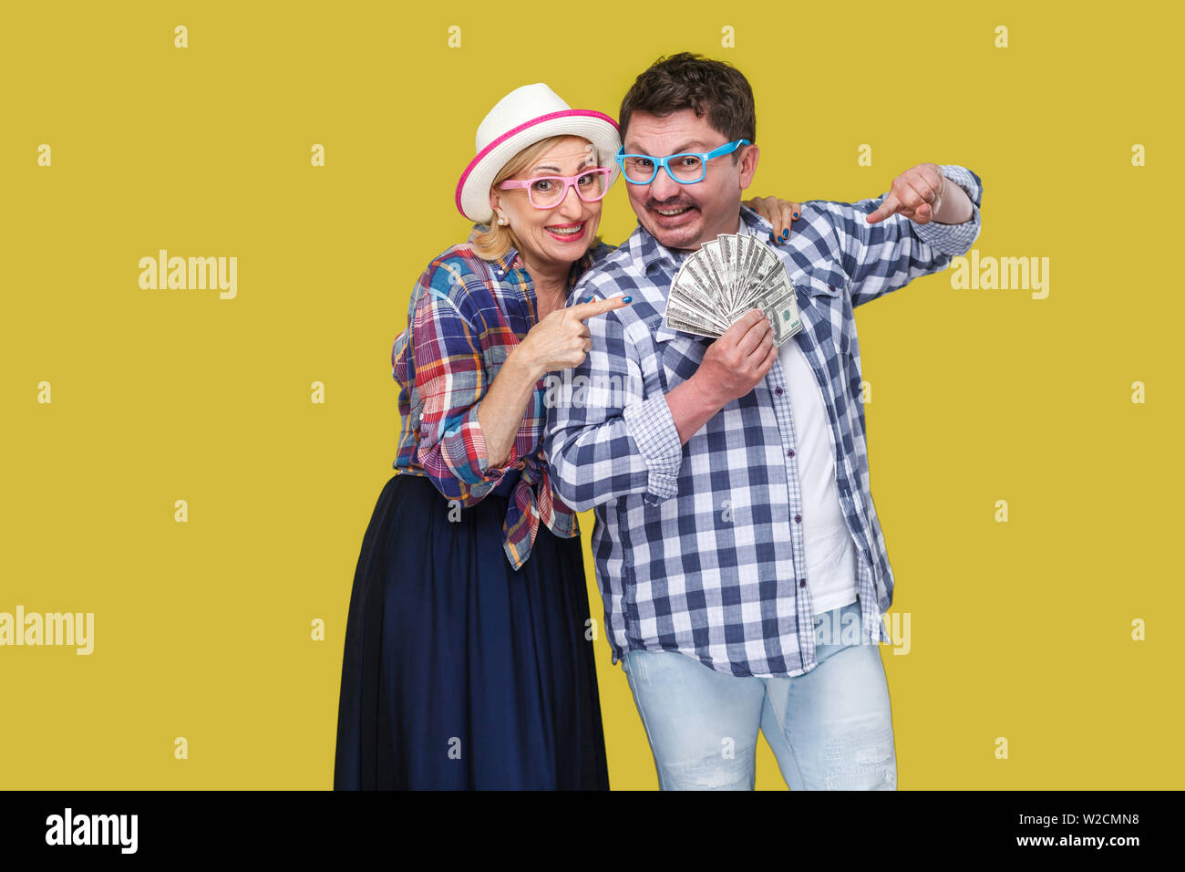 Happy wealthy family, adult man and woman in casual checkered shirt standing pickaback together, holding fan of dollar and pointing finger to money. I Stock Photo