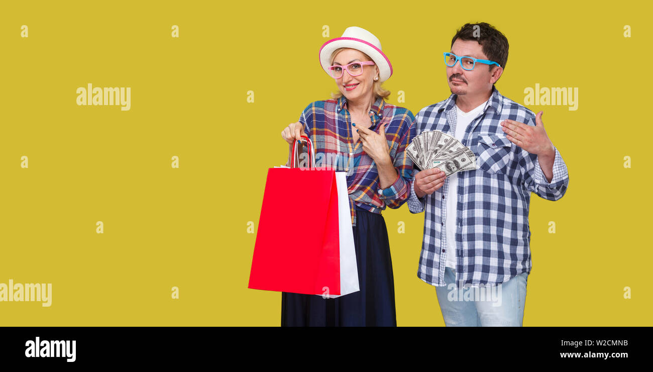 Happy family after shopping, adult man and woman in casual checkered shirt standing together,wife holding paper bag with toothy smile,husband fan of m Stock Photo