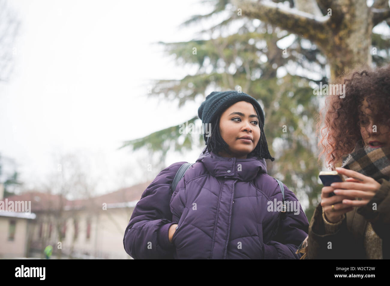 curly woman standing in park with friend and using smartphone – winter day, technology, curiosity - Stock Image
