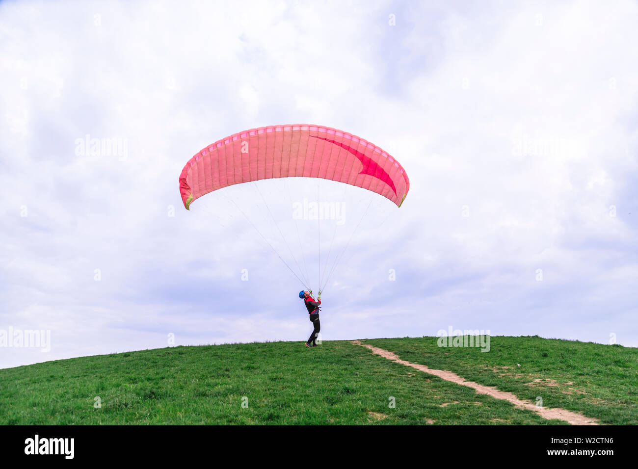 Man landed and tries to drop parachute on ground Stock Photo
