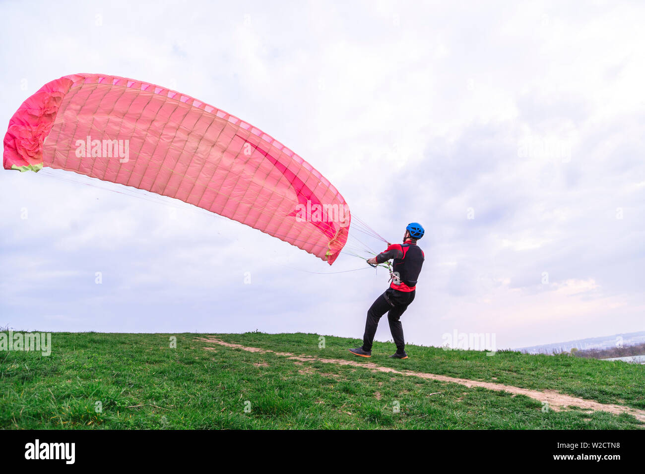 Man lowers paraglider to ground after landing Stock Photo