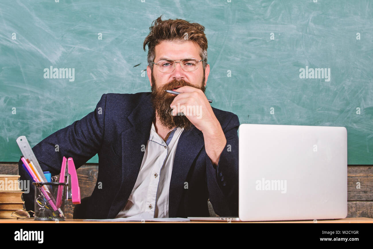Pay attention to details. Teacher concentrated bearded mature schoolmaster listening with attention. Teacher listening answer or report. Teacher formal wear sit table classroom chalkboard background. - Stock Image