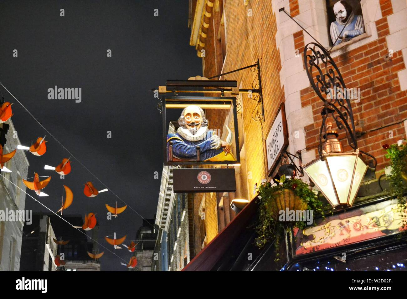 London/UK - November 28, 2013: Close-up view Shakespeare's head pub in the Carnaby street decorated for Christmas with red birds to feel happiness. Stock Photo