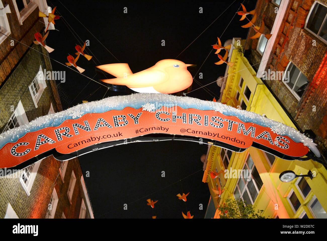 London/UK - November 28, 2013: Carnaby street in London decorated for Christmas with red banners and birds, making the perception more happy. Stock Photo