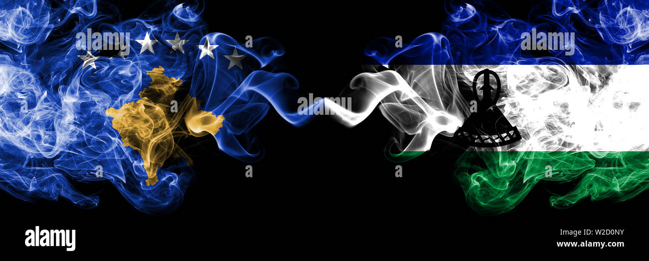 Kosovo vs Lesotho smoky mystic flags placed side by side. Thick colored silky smokes combination of Kosovo and Lesotho flag Stock Photo