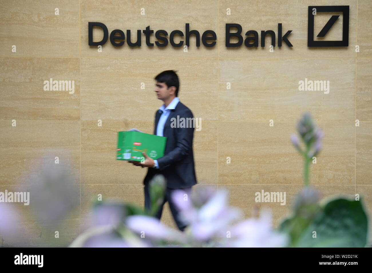 A man carries a box as he leaves a London office of Deutsche Bank which has confirmed plans to cut 18,000 positions across its global business, causing thousands of workers in the City of London to fear for their jobs. - Stock Image