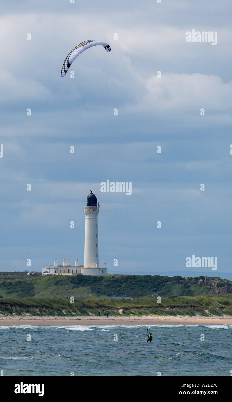 7 July 2019. Lossiemouth West Beach, Moray, Scotland, UK. This is person Kite Boarding at sea near Covesea Lighthouse in the Moray Coastline. - Stock Image