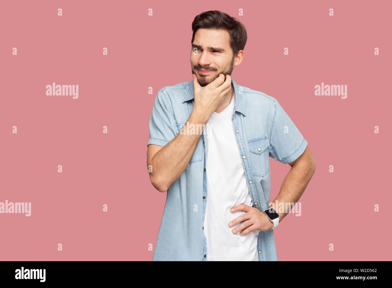 Portrait of confused handsome bearded young man in blue casual style shirt standing scratching beard and thinking what to do or try to find answer. in Stock Photo