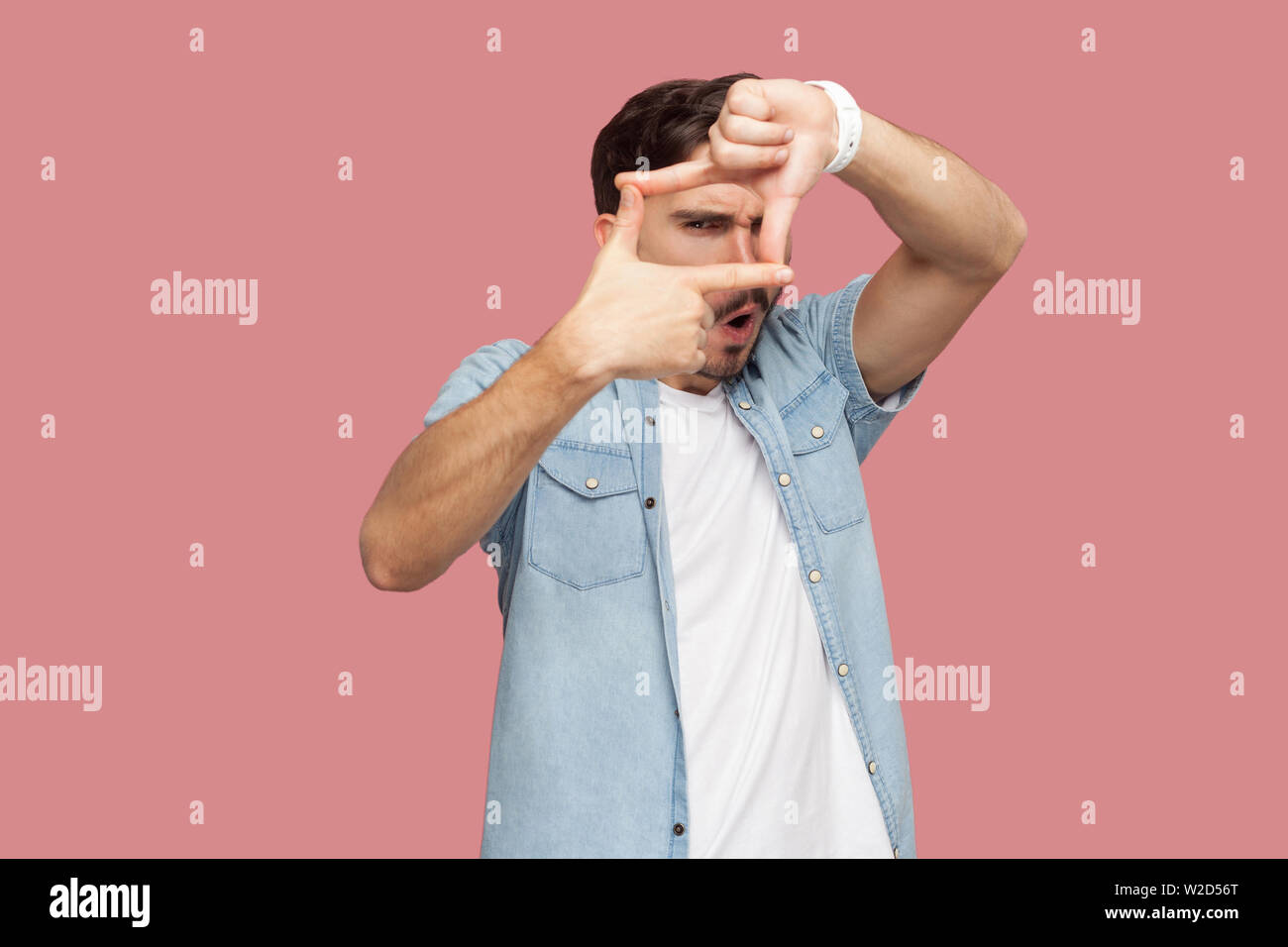Portrait of attentive handsome bearded young man in blue casual style shirt standing crop composition focus hand gesture and looking at camera . indoo Stock Photo