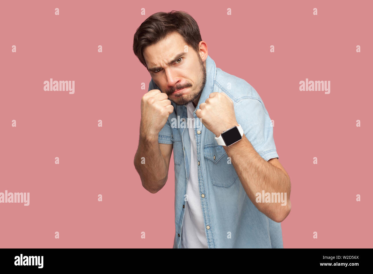 Portrait of angry handsome bearded young man in blue casual style shirt standing with boxing fists and looking at camera and ready to attack. indoor s Stock Photo