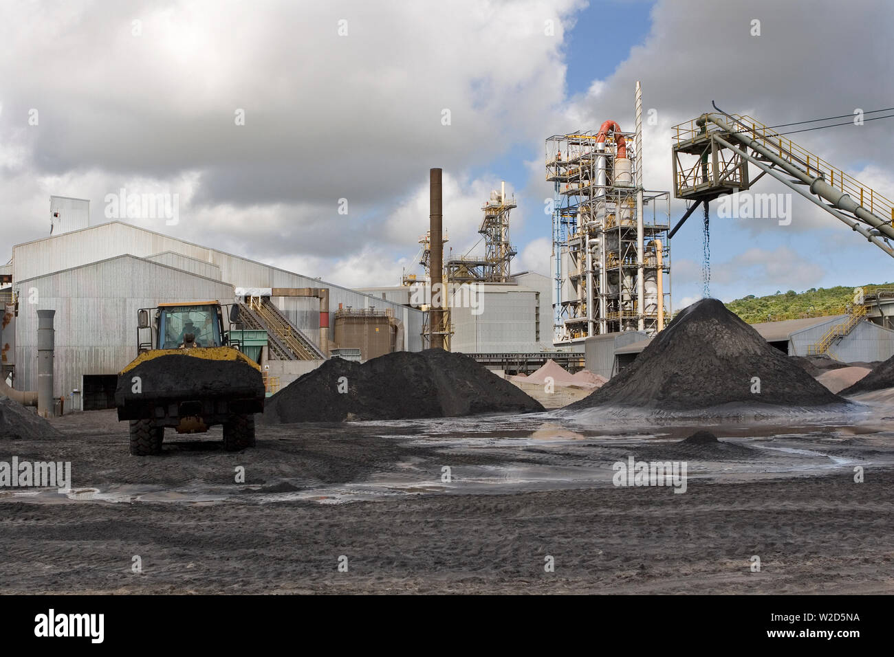 Mining, managing & transporting of titanium mineral sands. Front end loader moving heavy mineral sand concentrate from stock pile to separator plant. Stock Photo