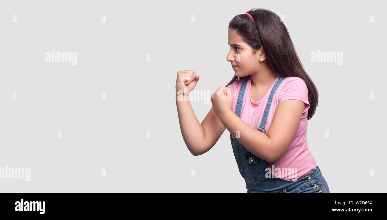 Profile side view portrait of serious or angry young girl in pink t-shirt and blue overalls standing with fists boxing hands and ready to attack. indo Stock Photo