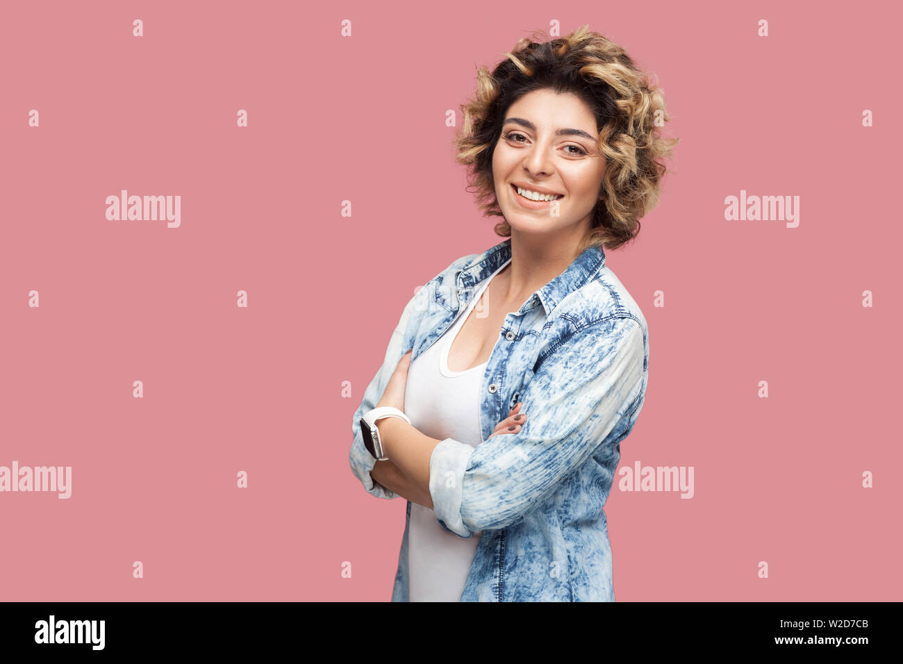 Portrait of beautiful successful happy young woman with curly hairstyle in casual blue shirt standing crossed arms and looking at camera, toothy smile Stock Photo