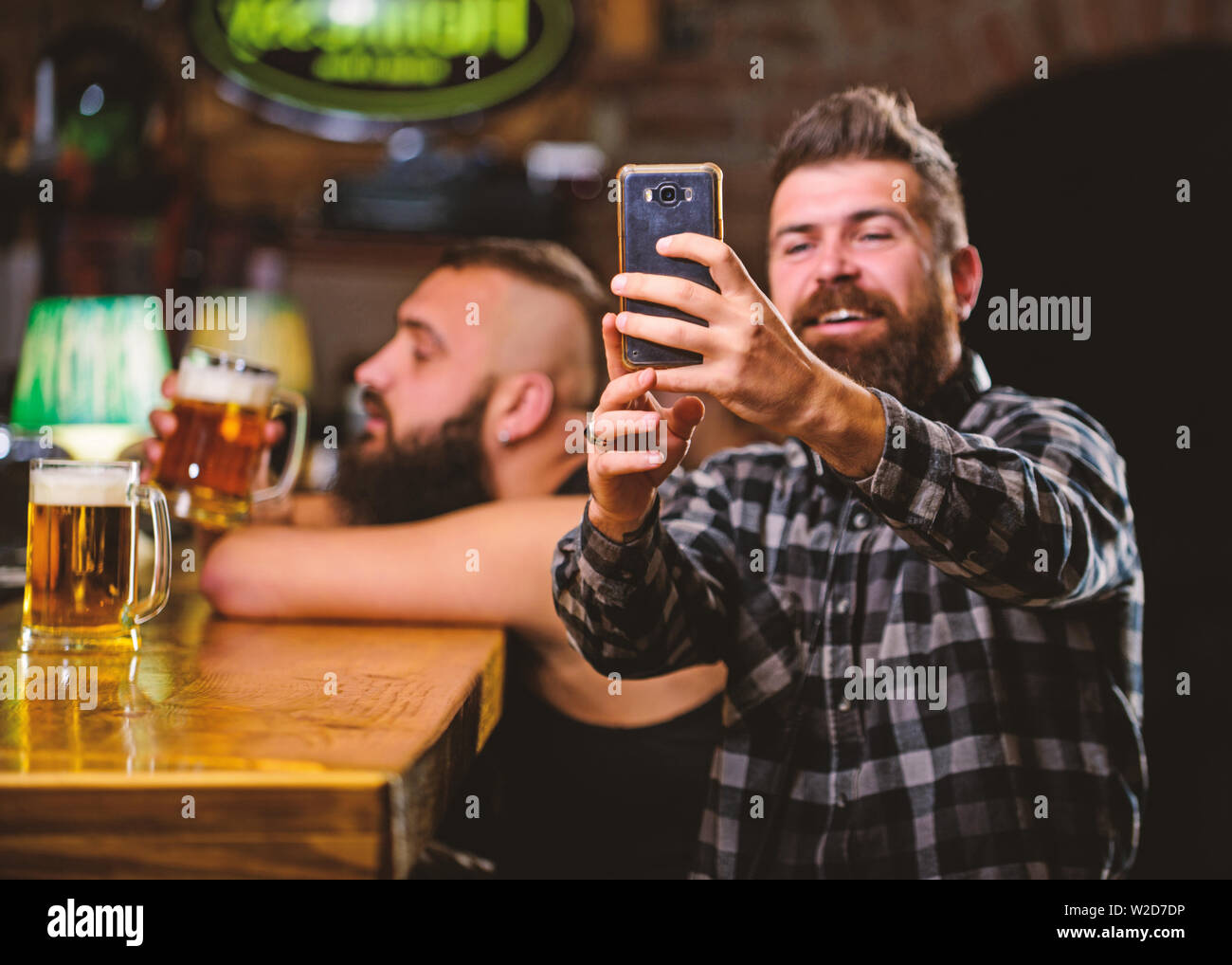 Online communication. Send selfie to friends social networks. Man in bar drinking beer. Take selfie photo to remember great evening in pub. Man bearded hipster hold smartphone. Taking selfie concept. - Stock Image