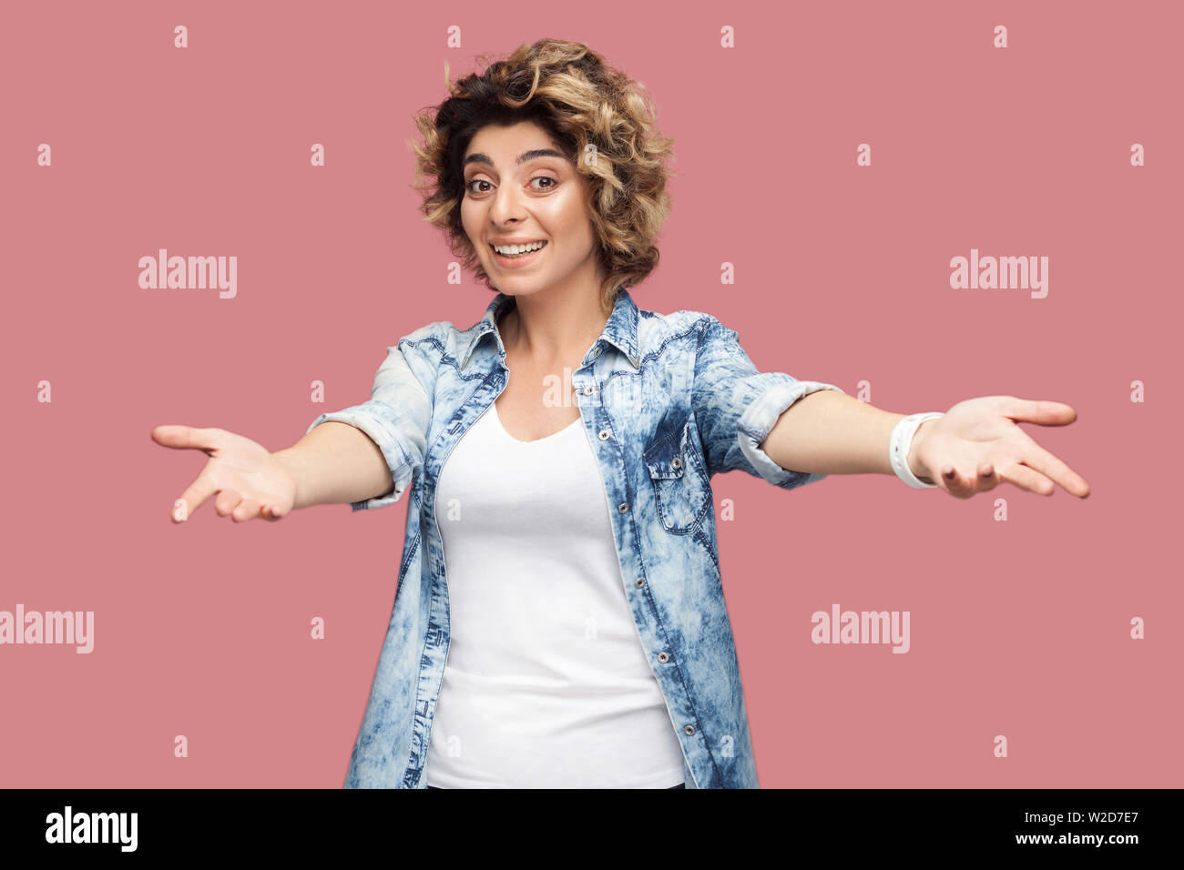 Portrait of happy young woman with curly hair in casual shirt standing with wide raised arms and looking at camera with toothy smile sharing something Stock Photo