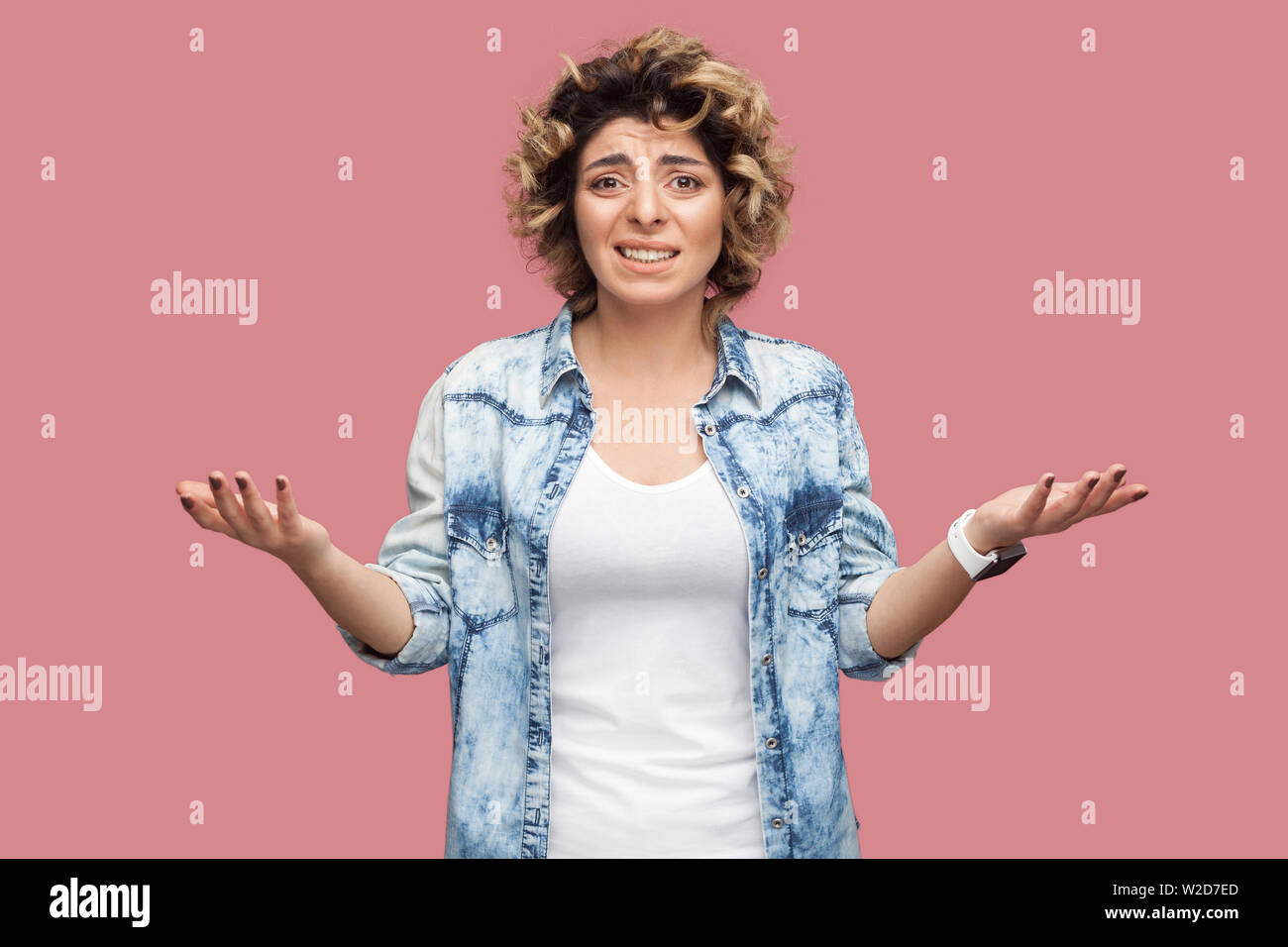 What? Portrait of confused or shocked young woman with curly hairstyle in casual blue shirt standing with raised arms and looking at camera worried. i Stock Photo