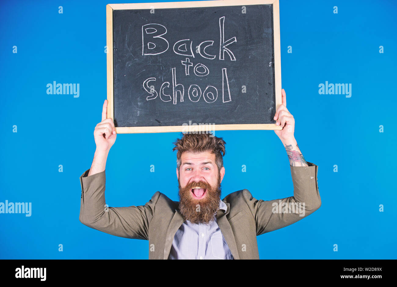 Teacher with tousled hair cheerful about school year beginning. Teacher bearded man holds blackboard with inscription back to school blue background. Keep working and be kind to people. Stay positive. - Stock Image