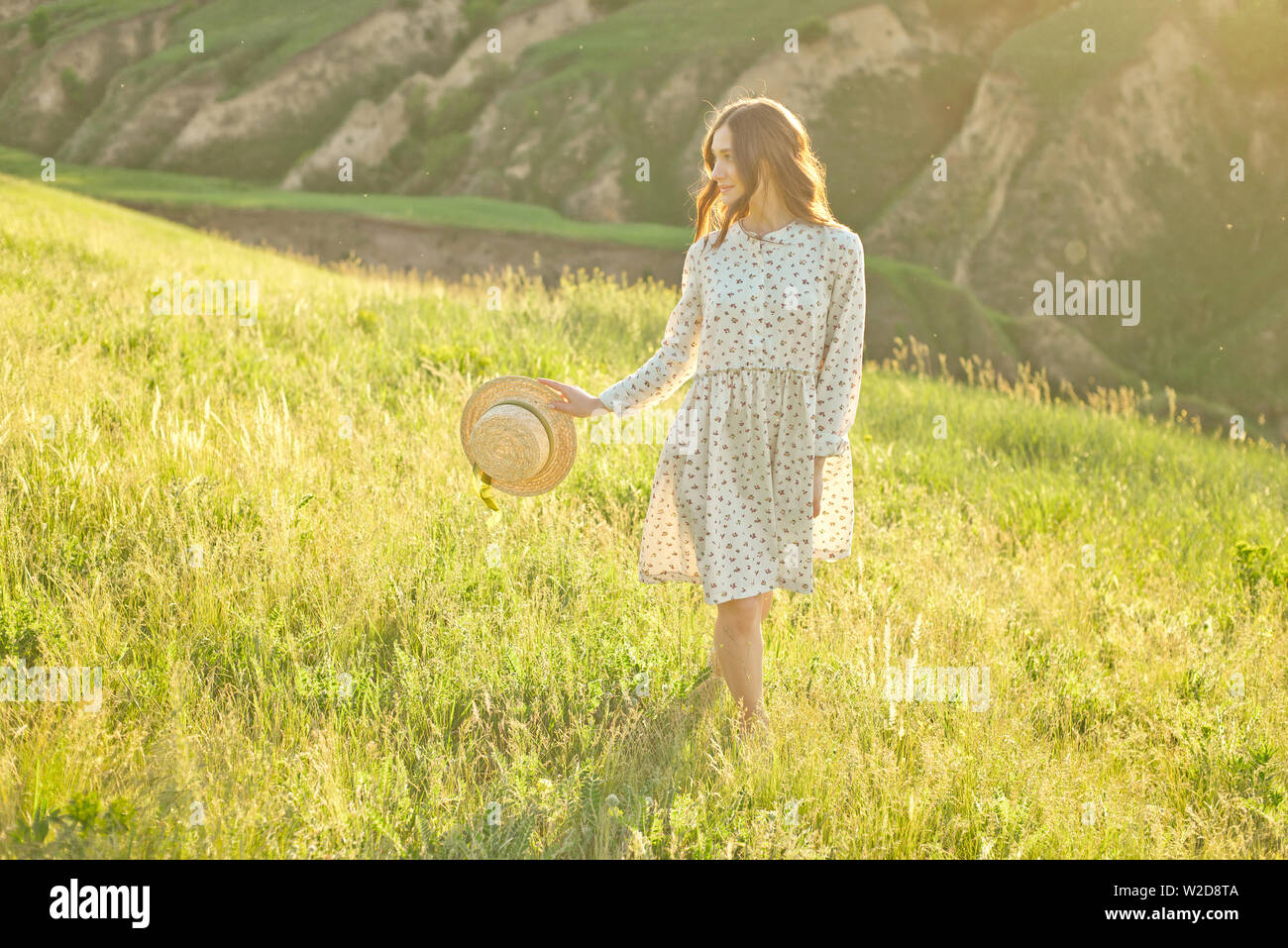 Beautiful girl in a summer sundress walks through the mountains in her hands holding a straw hat enjoying the rays of the sunset - Stock Image