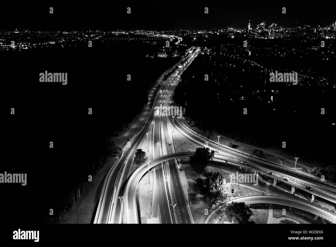 Aerial drone night shot of multilevel illuminated ring highway road junction leading to the sea. Black and White - Stock Image