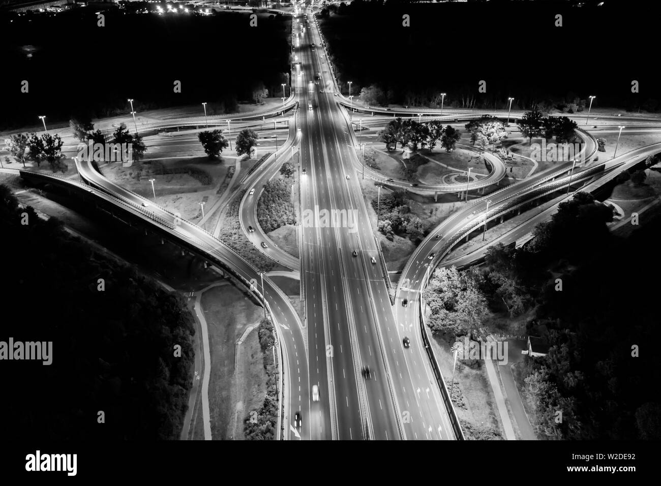 Aerial top view interchange of a city at night, Expressway is an important infrastructure in city, Road interchange in the city at night with vehicle - Stock Image