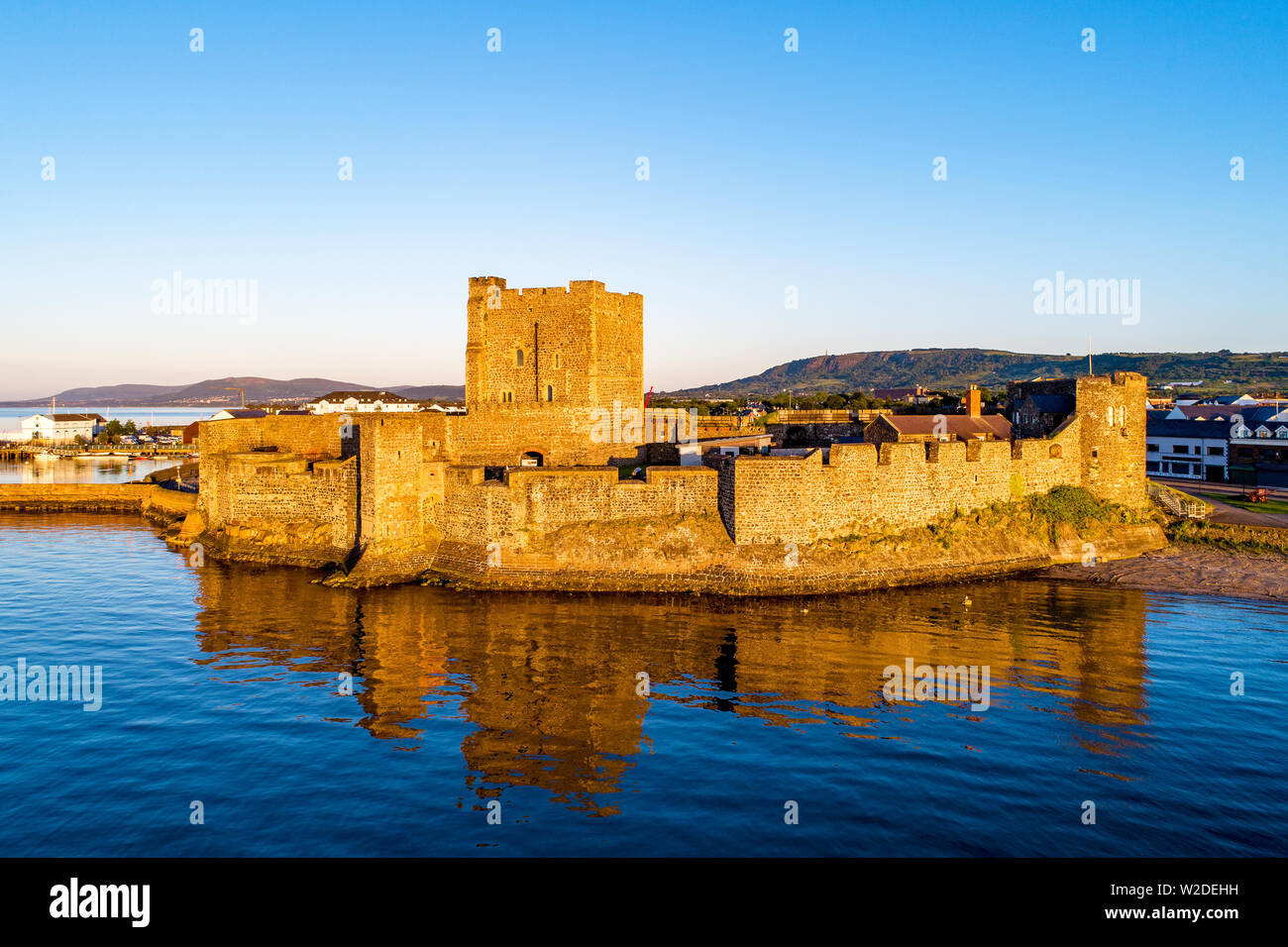 Medieval Norman Castle in Carrickfergus near Belfast in sunrise light. Aerial view with water reflection - Stock Image