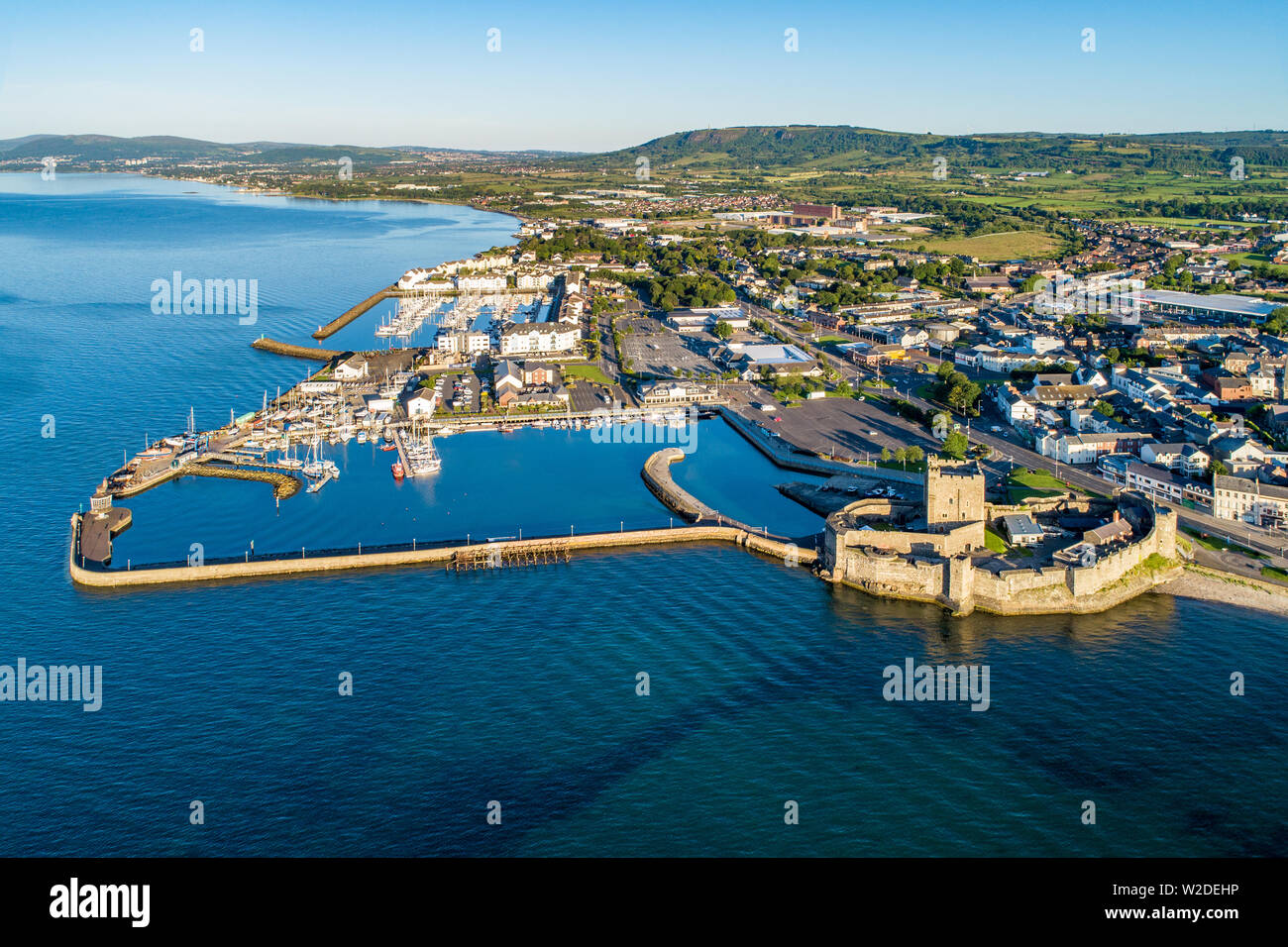 Medieval Norman Castle in Carrickfergus near Belfast in sunrise light. Aerial view with marina, yachts, parking, town and far view of Belfast in the b - Stock Image